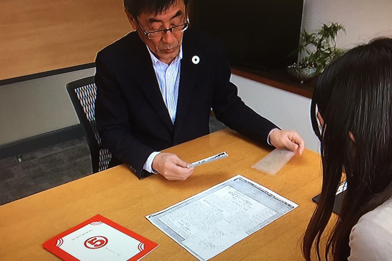(株)丸五の藤木茂彦社長。100周年机にはパンフレットが